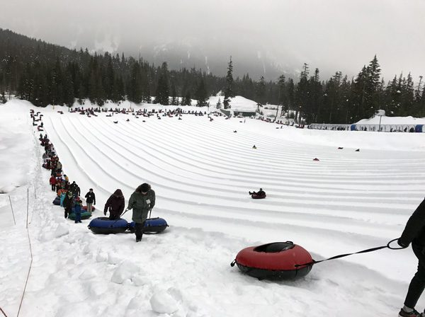 Snoqualmie Summit Tubing Center line of riders walking back up hill