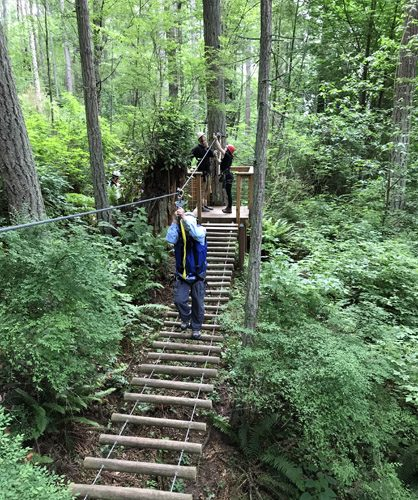 Canopy Tours Northwest zip line tour on Camano Island walking across log bridge