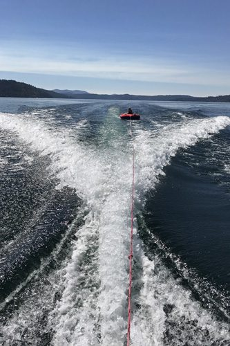 Lake Coeur d'Alene water inner tube pulled behind speed boat