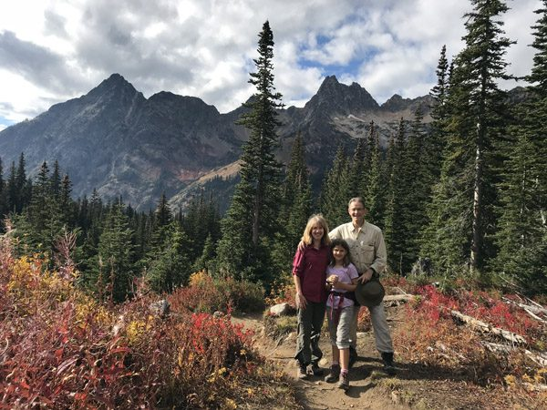 Family hiking up Blue Lake Trail with multi-colored fall meadows