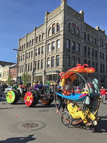 Port Townsend Kinetic Sculpture Race parade on Water Street with Mediocre Joker and floating fisherman