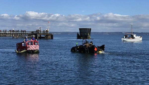 Port Townsend Kinetic Sculpture Race parade on Water Street with railroad car and Hatmobile in water race by pier