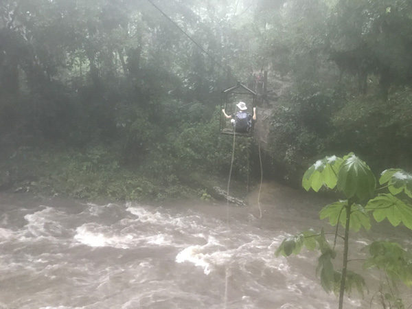 Hiker crossing over rain swollen river on aerial hand pulled cable car by trail to The Lost City Cidudad Perdida