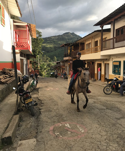Local cowboy riding prancing horse through streets of Jardin Colombia
