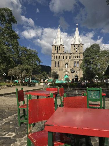 Main plaza tables and Basilica Menor de la Inmaculada Concepcion church in Jardin Colombia