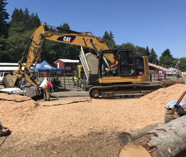 Log show with spoof improperly parked truck crushed by excavator at Whidbey Island Fair