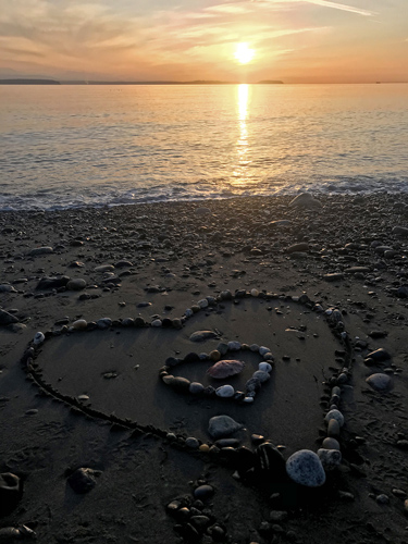 Sunset over Whidbey Island Puget Sound west side beach with heart design of rocks