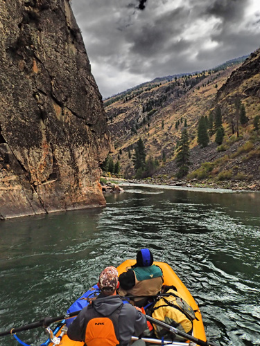 Rafting by sheer canyon wall on Middle Fork of Salmon River in Idaho